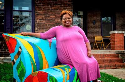 A photo of Crystal Wilkinson sitting on a couch in the front yard of a home.