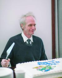 Dr. Lipscomb's son cuts a cake.